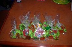 "Terraria party goody bags -- green paper filler, copper chocolate coins, green chocolate coins, Hershey's ""gold bricks.""  Plus some other non-Terraria stuff."