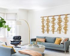 Transitional living room features a mid century modern vibe in a long dark gray sofa with mustard yellow pillows accented with a vintage woven wall hanging art. Tables Étroites, Living Room Sofa, Living Room Decor, Dark Gray Sofa, Drum Coffee Table, Pacific Heights, Yellow Pillows, Arc Floor Lamps, Transitional Living Rooms