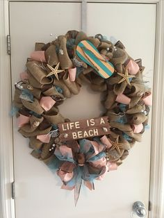 Island wreath with teal and peach ribbon starfish and sea shells and beach board.