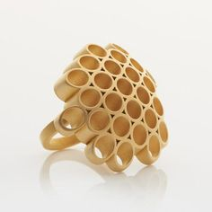 This bold statement ring features a honeycomb-inspired pattern that is elegantly sculptural. Handcrafted from sterling silver with 18ct gold plate and featuring