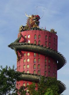 """The amazing """"Wat Samphran"""" temple in Bangkok:  At first sight this looks like a highly commercial attraction you would expect to see in Disneyland. However nothing is further from the truth as this unique temple is actually far off the beaten tourist path and is often excluded from tourist guides. The building is about 17 stories tall, with a giant dragon spiraling to the top. It's grounds include many sculptures of other beasts and a giant bronze Buddha."""