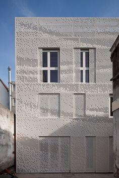 Social housing in Amsterdam, naar achter geplaatste panelen geven zelfs gesloten structuur aan de gevel.