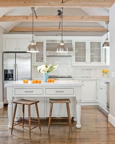 simple white kitchen:  exposed natural wood beams; stools; pine floors; like the drawers in island