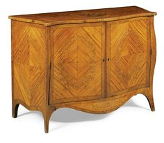 A George III satinwood and marquetry serpentine bombé commode circa 1780 the quarter-veneered oak crossbanded top inlaid with a basket of flowers, with two doors enclosing a shelf and inlaid with floral wreaths, the sides inlaid with wreaths of husks  Sotheby's
