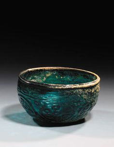 A FATIMID DEEP SEA GREEN GLASS BOWL  EGYPT OR SYRIA, 10TH CENTURY  Of rounded form with inverted base and stepped rim, the sides moulded with simple roundels each containing six circles around a central circle, further circles in the interstices above and below, a minor band with ovals above and similar band of circles around the foot, intact, original surface, areas of creamy iridescence, fitted case  7¼in. (18.4cm.) diam.