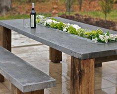 Bank und Tisch mit Blumenkasten aus Holz und Beton mit Weinflasche