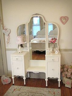 This tri-fold vanity is pretty with all its delicate details especially the carved floral appliques at the top and bottom of the tall mirror. The two top drawers and two lower cabinet doors feature newly added glass knobs. The vanity is refinished a cottage white and lightly distressed.
