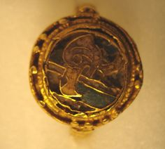 Gold finger-ring: an eagle design on the bezel in yellow, blue and purple cloisonné enamel, surrounded with pellets.