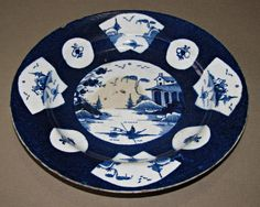 A Bow porcelain plate, powdered blue, chinoiserie landscapes, circa 1760 Mock Chinese characters on base. A similar example is in the V&A collection. See http://collections.vam.ac.uk/item/O279132/plate-bow-porcelain-factory/  Circa 1758-1762.  22.5cm diameter (approximately 9 inches) / 3cm deep  In original condition with no restoration. One hairline issuing from rim, two small chips to rim, utensil marks, stains and typical firing marks £71