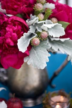 I like the idea of a dusty miller centerpeice in mismatched metal jars or vases. I want the textures to clash, if that makes sense