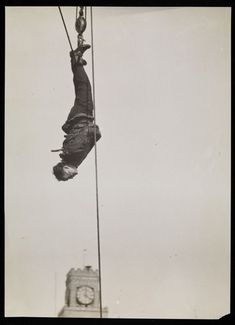 Houdini hanging by his feet above the clock tower in Times Square, New York…