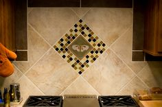 The Even's family created this kitchen back-splash focal point using my Moth Tile on point framed with glass tile.