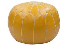 Moroccan Leather Pouf, Saffron Yellow -- Handcrafted in Morocco, this ottoman is a luxurious home accessory. Individual pieces of leather are dyed, then stitched together and embroidered by hand. The bright saffron pouf is filled with dense cotton for extra durability.
