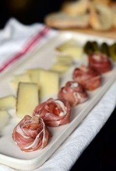 Prosciutto rosettes.  Take a piece of prosciutto and twist into a long strand.  • Then wrap it tightly into a rosette, tucking the end underneath if necessary to keep it from unrolling.