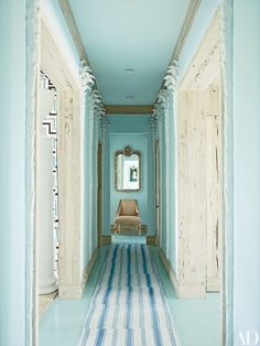 A hallway in this Bahamas beach home by designer Miles Redd, painted in a Benjamin Moore blue, is lined with plaster palm trees; rugs from IKEA were stitched together to make the runner.