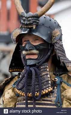 Man dressed in full samurai armor complete with kabuto helmet and mempo face mask to intimidate the enemy Stock Photo