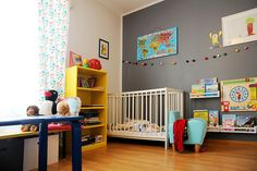 Gray accent wall + brightly colored furniture that can be repainted as child ages + soft beads above crib + books low on the wall [for anybody wondering, they're sitting in IKEA spice racks] = brilliance.