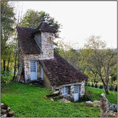 A stone cottage on the side of a hill.