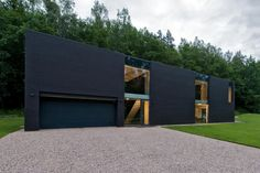 leibal:  Family House in Minsk is a minimalist residence located in Minsk, Belarus, designed by Architektu biuras G.Natkevicius ir partneriai. The black monolith volume is interrupted by large glazings that reveal the interior artwork and furnishings. One side of the building consists of large transparent sliding doors that provide access to the outdoors. The interior is composed mainly of darker elements with contrasted white walls and accents.