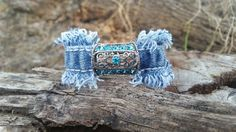 This bracelet has a pretty centerpiece with aqua blue bling. The back has very sparkly clay beads with Czech rhinestones. The silver beads are charms that dangle.