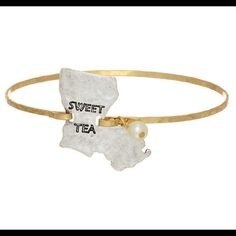 "Louisiana Shaped Bracelet With ""Sweet Tea"" Stamp Gold tone bangle bracelet featuring a silver tone state of Louisiana stamped ""SWEET TEA"" with a faux ivory pearl accent. Jewelry Bracelets"