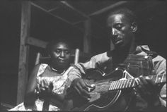 Blues legend Mississippi Fred McDowell and his wife Annie Mae McDowell, on the porch of his house in Como, Mississippi. This photo was taken in the fall 1959. | Photo Credit: Alan Lomax | Association for Cultural Equity