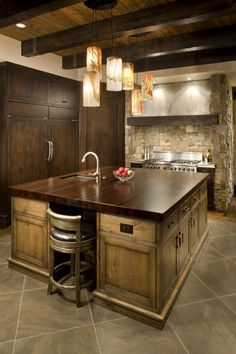 This kitchen, a combination of rustic and contemporary style, features pewter countertops, distressed alder cabinetry, a wenge-wood island, and Wolf & Sub-Zero appliances