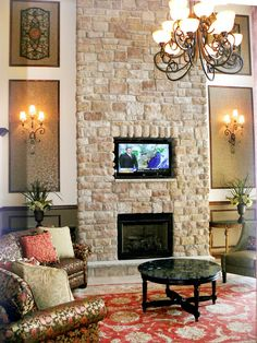 This textured stone wall is centered in a traditional living room, accented by elegant lighting and designer furnishings. Decorative wall frame molding is given a facelift by adding metallic wallpaper to the inside of the frame.