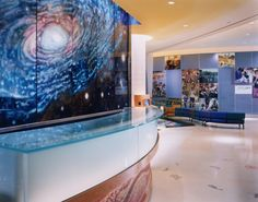 """The child is the focus and driving force behind this design, which encourages curiosity, wonder, and learning. A """"You Are Here"""" map pinpoints the hospital's location on an enormous glass mural of our galaxy. On each floor, artist installations relate either to the developmental level of the child or the illness treated there. The hospital reflects the philosophies of family-centered care and the teachings of Carl Sagan, stressing our connection to the entire universe."""