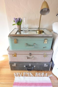 Sweet side table made from cute, colorful antique suitcases, with the table top made of glass decorated with flowers and a lamp.