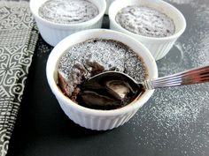 Instant Pot chocolate lava cake with powdered sugar and spoon scooping out gooey center in ramekin and two other ramekins in background with black and white napkin on black surface - Paint the Kitchen Red