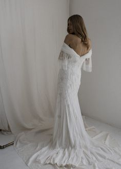 ISLA Off The Shoulder Wedding Dress | Bo and Luca  The elegant, fit and flare ISLA gown is made from delicate layers of the softest Tulle and Silk. This fully beaded wedding gown features an off-the-shoulder design with gathered Toft tulle on the bust line before dropping down into tiered beaded bell sleeves. The gown hugs the the body through the bust, waist and hips before draping down in soft layers from just above the knee into an elegant train.
