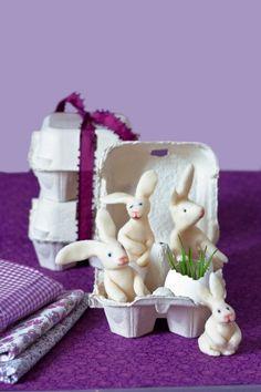 Des lapins blancs en pâte d'amande dans une boîte à œufs pour Pâques.