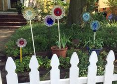"Six DIY flowers made from plates, jello molds, glass wear in different colors sitting ""planted"" outside of a yellow house with a white picket fence in front of them"