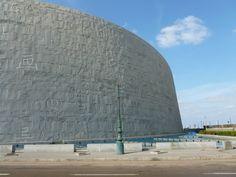 Fasade i stein på Alexandria Biblioteket. Hele fasaden til Alexandria biblioteket er preget av huggede tegn og symboler. Johansen Monumenthuggeri AS bisto med opplæring av egyptiske steinhuggere og hugging av symbolene.