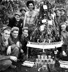 American soldiers at an advanced medical dressing station celebrate Christmas during the Battle of Buna-Gona with a handmade Christmas tree made of palm leaves and decorated with surgical cotton wool, rations, cigarette cartons and post cards. Buna, Oro Province, Papua New Guinea. 25 Decembr 1942. Image taken by George Silk.