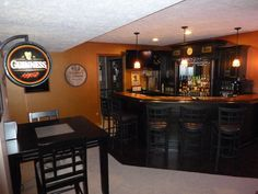Basement Irish Pub. Love the black cabinets and using the corner! It makes the bar bigger when you wrap it around.