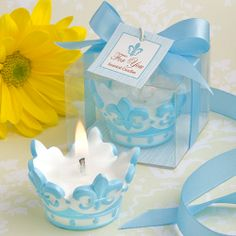 These Blue crown design scented candle favors are a royal match for baby showers, Christenings and any baby-boy themed event. A white wax, floral scented candle features baby blue details. The top is carved with blue fleur de lis forming the tips of a crown while blue circles and triangles surround the base. The favor comes beautifully packaged in a clear topped display box with a blue and white design background insert. Wrapped in a baby blue satin ribbon with an attached fleur de lis…