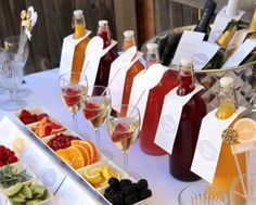 dishes of fruit and herbs sit in front of a row of fruit juices in glass jars for a festive mix and match mimosa bar