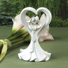 $19.95 - A couple united as one and surrounded by the personification of love holds a bouquet of calla lilies, creating this elegant cake topper. Perfect to coordinate with a wedding centered around a Calla Lily theme.