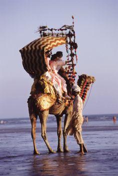 Pakistan, Sind, Karachi, Clifton Beach, Family taking camel ride on beach.