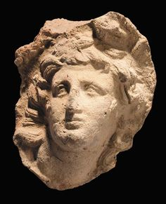 A HELLENISTIC TERRACOTTA ROUNDEL WITH PORTRAIT HEAD OF ALEXANDER THE GREAT IN HIGH RELIEF  3RD CENTURY B.C.   The deified ruler shown in classic pose with head turned upwards and slightly back to his right, his gaze held aloft, his face sensitively modelled with full mouth, arched and furrowed brow framed by long flowing locks, mounted