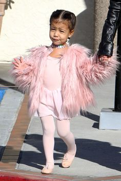 North West schools us all on ballet class style, stepping out in a pink fur coat, diamond choker and pink leotard.