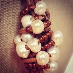 Detalle de collar marrón con perlas y piezas metálicas en color cobre