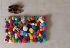 DIY Inspiration Idea Pom Pop Rug - Sew Multicolored Pom Poms Made From Yarn Onto Hessian Or Burlap Fabric. Apply Non-Skid Backing To Bottom Of Rug
