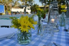 Want a cute country feel for your #wedding? Try #blue checkered tablecloths, perky #yellow flowers, and lanterns for table #decor.