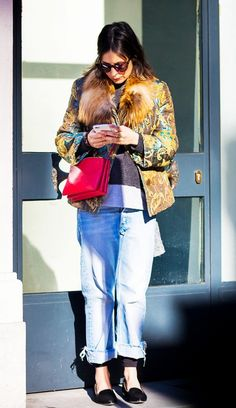 A layered t-shirt and sweater is worn with a brocade jacket, cuffed jeans, flats, and a red bag