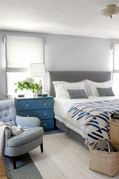 """Bed: The sisters reupholstered the orange headboard in Brochier's gray cotton twill, then moved the bed to a different wall, where it now sits between two sunny windows. Seema Krish pillows and an antique quilt from Laura Fisher top the bed.  Nightstand: An Ikea bureau—which Lisa covered with wallpaper by Anya Larkin—serves as both a bedside table and a spot to store everything from socks to magazines. The ceramic rooster lamp is a vintage find. Chair: """"I scored this at a tag sale for $10,""""…"""