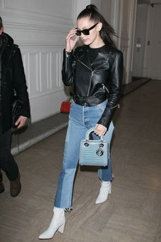 Bella Hadid paired a leather jacket with jeans, white boots and a Dior handbag for an outing in Paris.