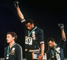 Extending gloved hands skyward in racial protest, U.S. athletes Tommie Smith, center, and John Carlos